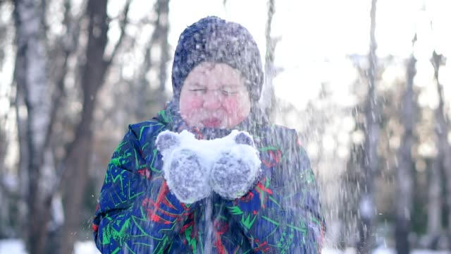 Teenage boy blowing snow from his hands.