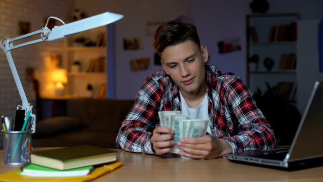 Teenage boy counting dollar bills thinking about new purchase, dreaming
