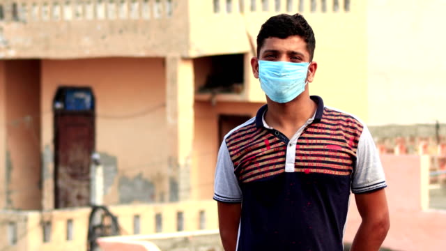 Teenage boy covering his face with pollution mask for protection from viruses video