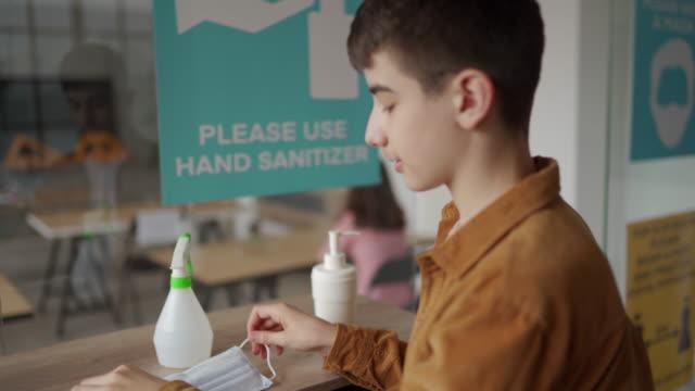少年用洗手液消毒雙手,在教室戴上防護面罩 - back to school 個影片檔及 b 捲影像