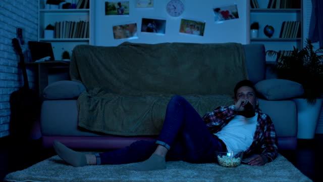 stockvideo's en b-roll-footage met tiener bier drinken en eten snacks kijken naar film, alcoholverslaving - kids online abuse