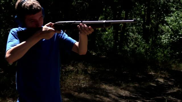 Teenage boy in blue shirt shoots rifle video