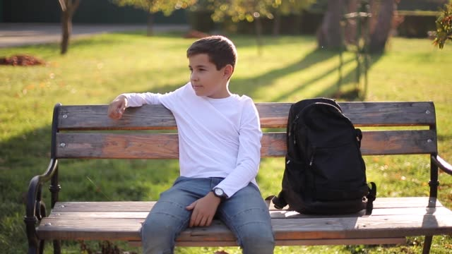 Teenage boy in white sweater sitting on the bench. Handsome school boy with backpack in autumn park Teenage boy in white sweater sitting on the bench. Handsome school boy with backpack in autumn park. sweatshirt stock videos & royalty-free footage
