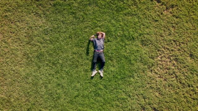 teenage boy lying on the grass using his smart phone - trawa filmów i materiałów b-roll