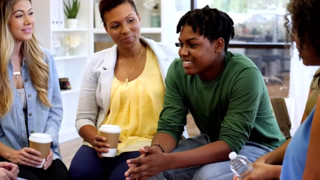 Teenage boy participates in group therapy session Cheerful African American teenage boy listen and responds to advice given to him during a group therapy session. He gestures as he responds to the advice. guidance stock videos & royalty-free footage