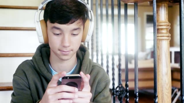 teenage boy plays mobile game on smartphone - cuffie wireless video stock e b–roll