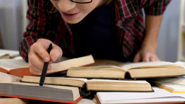 Teenage boy reading paper books instead of internet, outdated education system video