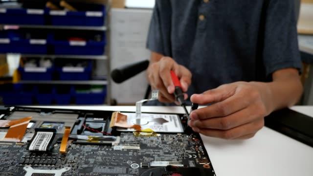 Teenage boy repairs laptop hard drive