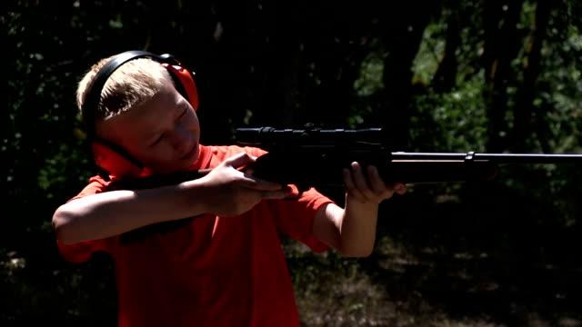 Teenage boy shooting a rifle video