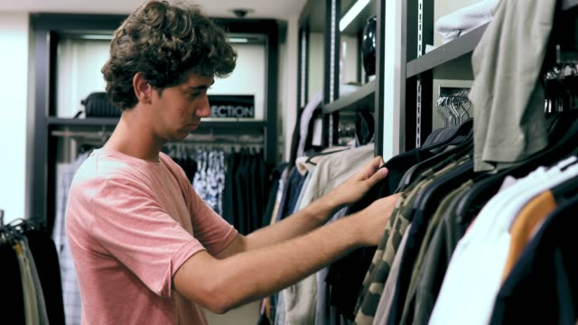 Teenage Boy Shopping Clothes On Summer Vacation Stock Video