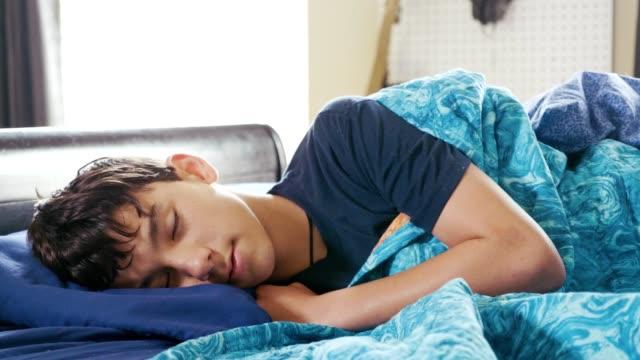 Teenage boy sleeps in on a Saturday morning video