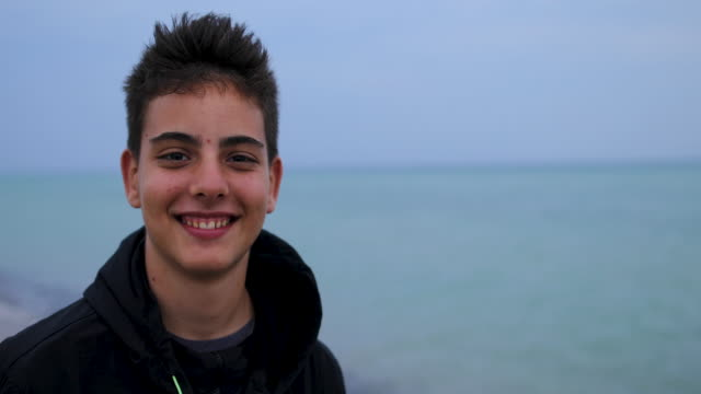 Teenage Boy Standing Near Sea, Looking At Camera And Smiling video