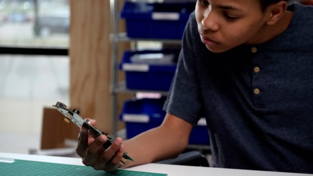Teenage boy studies computer part