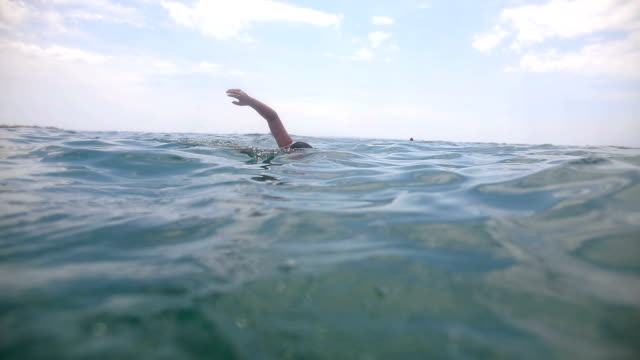 teenage boy swimming in the ocean doing breastwork - nuoto mare video stock e b–roll