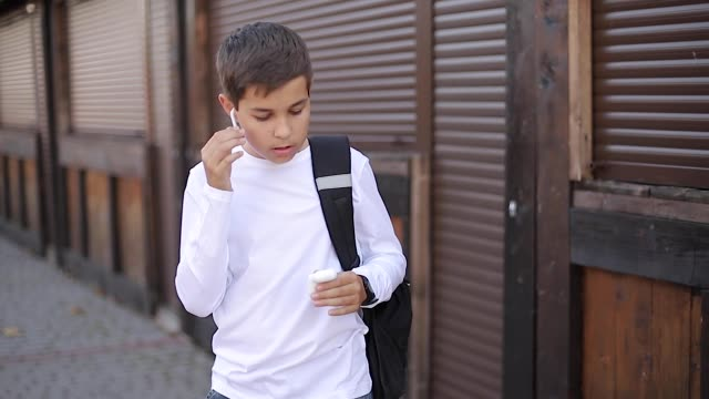 teenage boy take out a wireless headphones and put then into the ears. young boy in white shirt with backpack. boy listen music - cuffie wireless video stock e b–roll