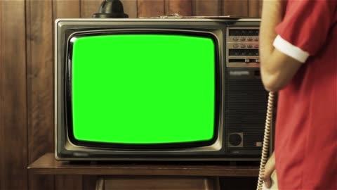vidéos et rushes de adolescent de parler au vieux téléphone près d'un téléviseur avec écran vert. - tradition