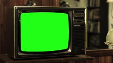 vidéos et rushes de adolescent de parler au vieux téléphone près d'un téléviseur avec écran vert. - format hd