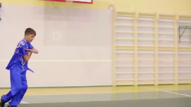 Teenage boy training wushu exercises Changquan.