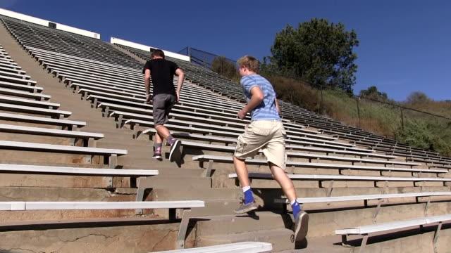 Teenage boys running up and down stadium stairs video