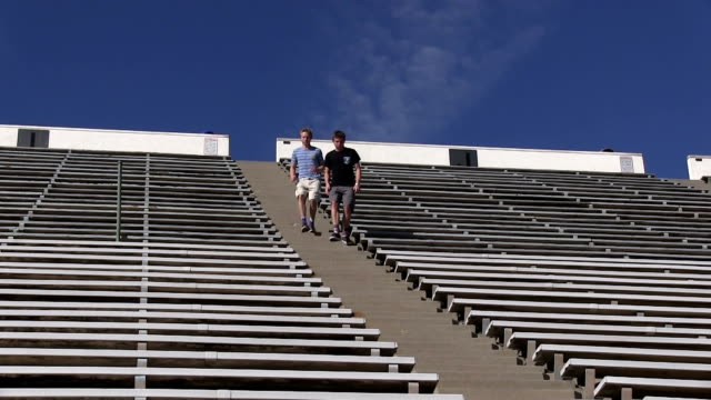 Teenage boys running up and down stadium stairs video