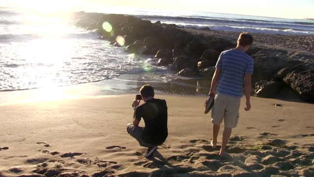 Teenage boys walking on beach and rock video