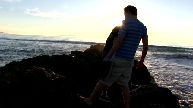 Teenage boys walking on California beach and rocks at sunset video