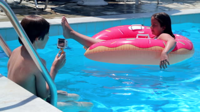 Teenage brother shooting video of younger sister in swimming pool, handheld shot video