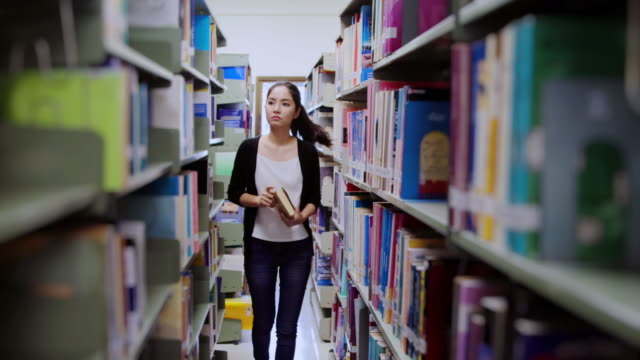 Teenage choosing a book in the library. video