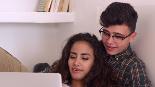 Teenage couple hanging out in bedroom watch laptop, close up, shot on R3D video