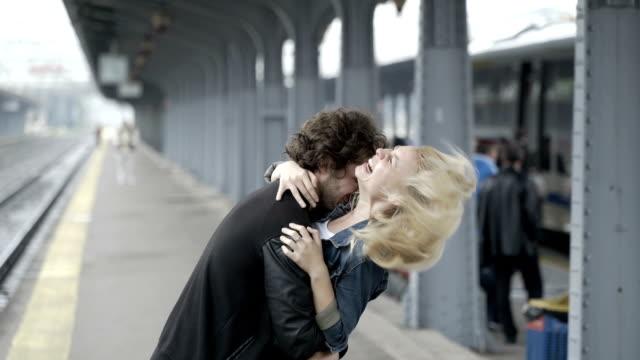 Teenager-Paar in Liebe kitzeln und küssen im Bahnhof vor der Abfahrt des Zuges warten Spaß – Video