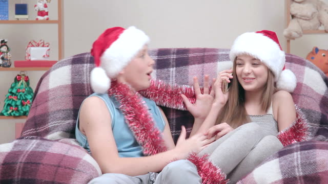 Teenage couple in Santa Claus hats talking on smartphone, smiling video