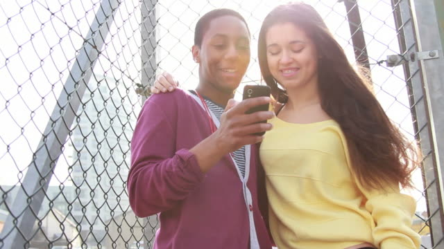 Teenage couple looking at mobile phone video