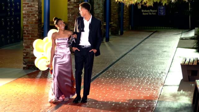 vídeos y material grabado en eventos de stock de pareja adolescente caminando juntos después del baile - baile de estudiantes de secundaria