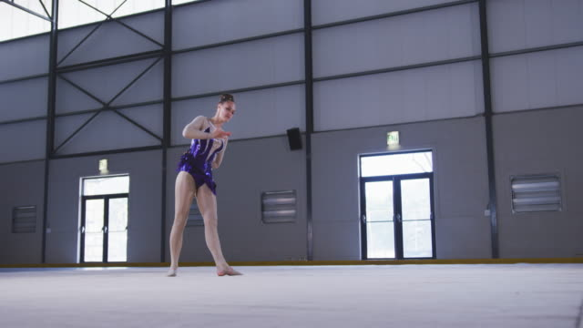teenage female gymnast performing at sports hall - леотард стоковые видео и кадры b-roll