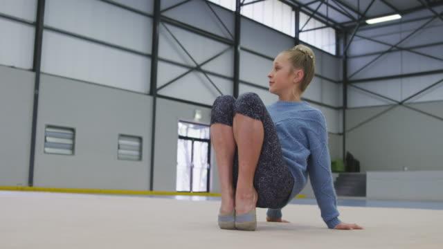 teenage female gymnast performing at sports hall - ludzka kończyna filmów i materiałów b-roll