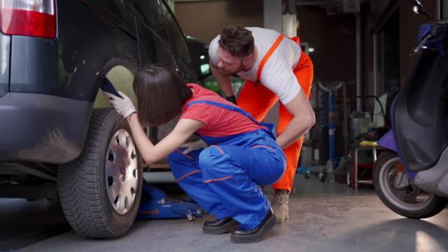 Teenage female mechanic fixing a tire in auto repair shop