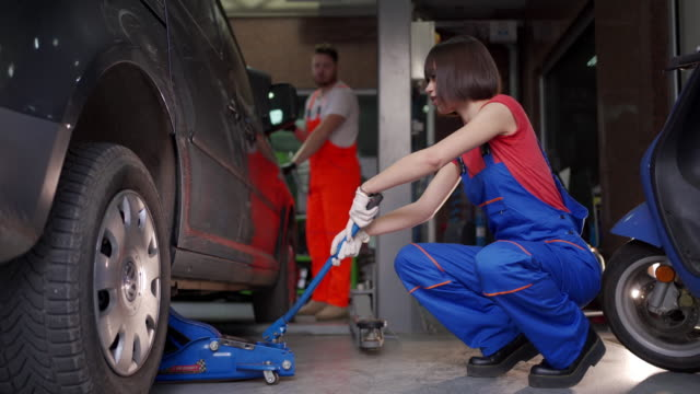 Teenage female mechanic inflating a tire