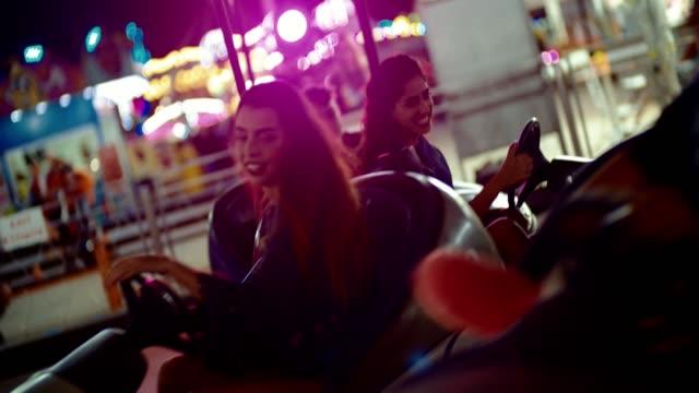 Teenage friends crashing at bumper cars ride at amusement park video