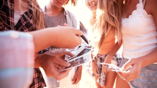 stockvideo's en b-roll-footage met teenage friends sharing photos in a group - polaroid