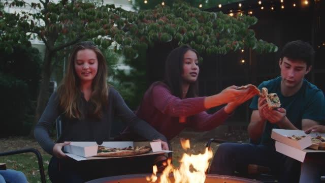 vídeos de stock, filmes e b-roll de sente-se amigos adolescentes rodada uma pira comendo pizzas take-away - festa no jardim