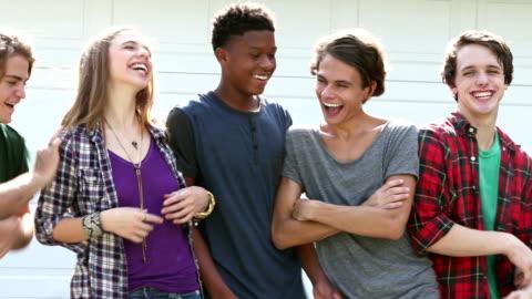 vídeos y material grabado en eventos de stock de adolescente y cuatro chicos en una fila, riendo, empujando - actividades recreativas
