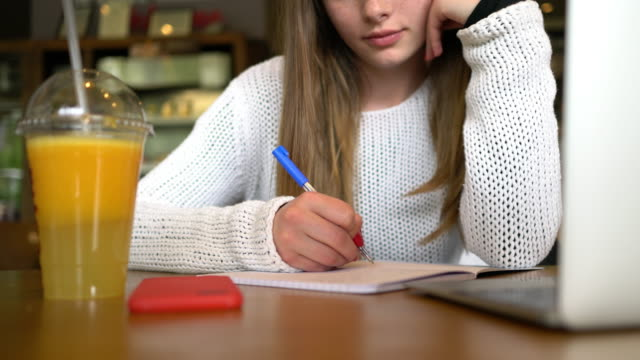 Teenage girl at cafe studying for exams video
