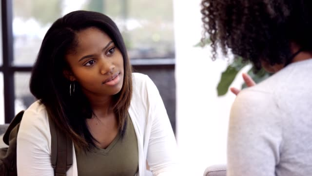 Teenage girl attentively listens to high school guidance counselor Attentive African American teenage girl nods her head in agreement as she listens to a mature female high school guidance counselor give her advice. The counselor gestures  while talking with the teenage girl. school counselor stock videos & royalty-free footage