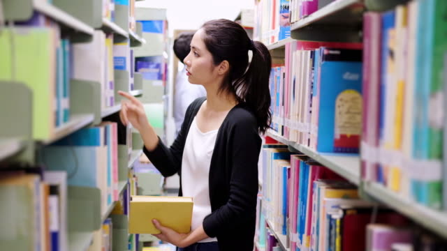 Teenage girl choosing a book in the library. video