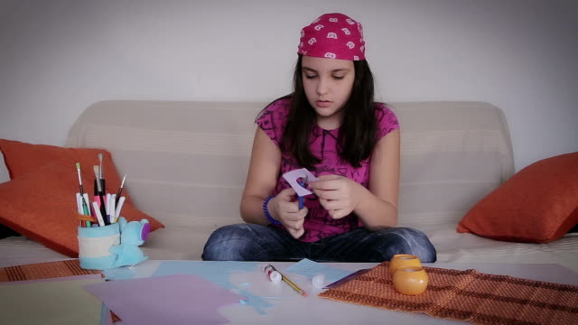 teenage girl cutting heart shape from paper,at home video