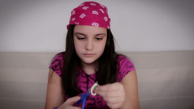 teenage girl cutting heart shape from paper,at home,closeup video