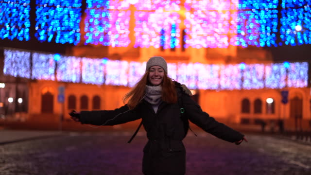 Video Teenage girl dancing outside at night celebrating Christmas