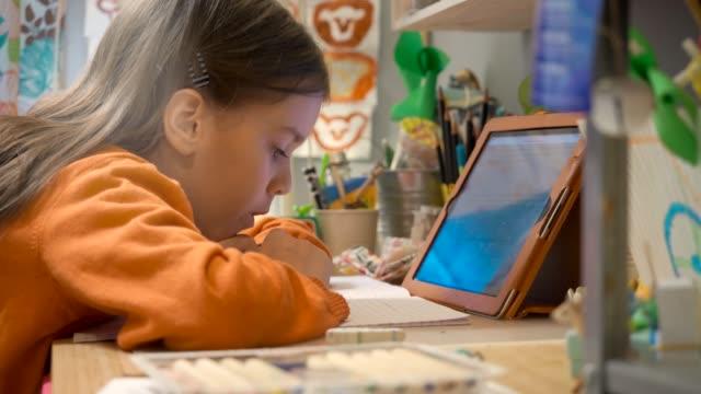 covid-19の間に自宅の隔離で学校の仕事ビデオオンラインレッスンをしている10代の女の子 - 人里離れた点の映像素材/bロール