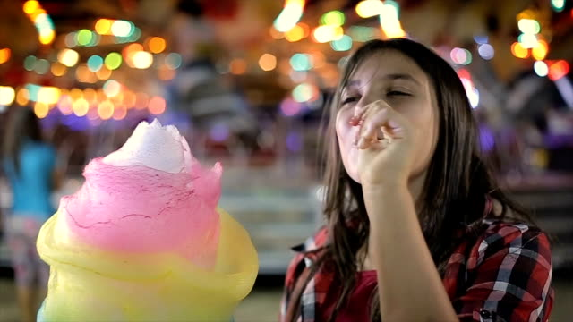 Teenage girl eating cotton candy in amusement park
