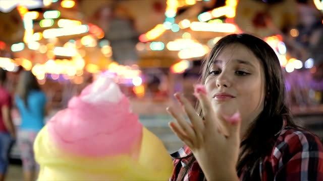 Teenage girl eating cotton candy in amusement park Teenage girl eating cotton candy in amusement park cotton candy stock videos & royalty-free footage